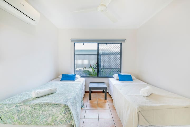 The well-lit third room offers two single beds and a bedside table, allowing the house to fit up to six guests