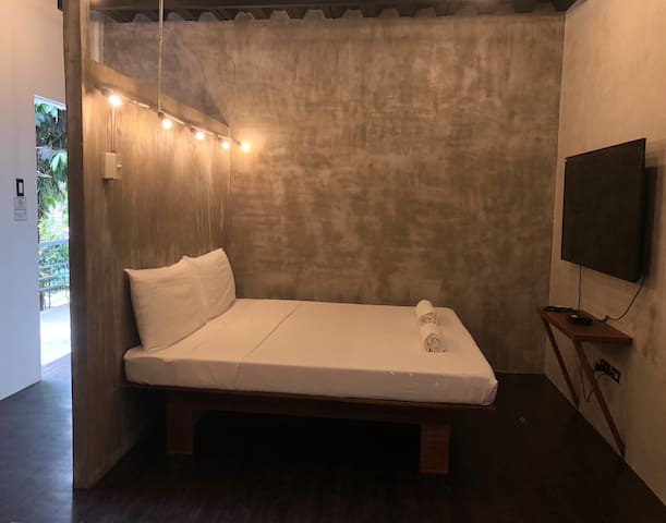 This is Studio Apartment 104.   It features a king-size bed, private bathroom with basic toiletries, kitchen with simple cooking utensils and dinnerware, plus a dining area. Guests are also provided access to free Wi-Fi and Netflix.