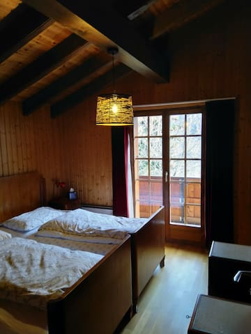 Chambre 1, orientée Sud, avec balcon. Deux lits simples. Complètement boisée, mansardée et haute de plafond. Chauffage d'appoint électrique. Les lits peuvent être écartés ou rapprochés.
