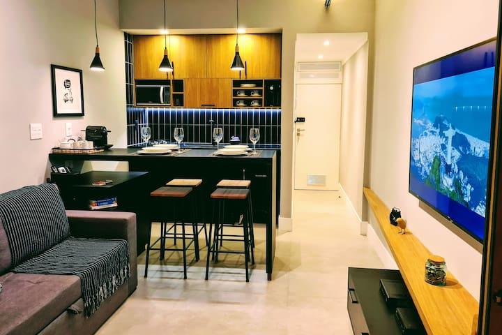 Living room equipped with queen size sofa bed, 65 inch Smart TV and a complete and functional kitchen.