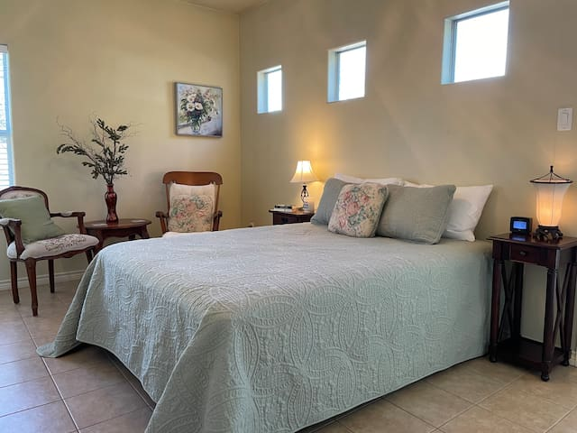Master bedroom with queen bed and a seating area