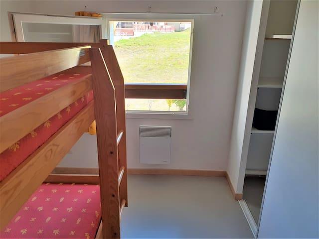 Petite chambre avec une fenêtre et un placard (penderie et 3 étagères).