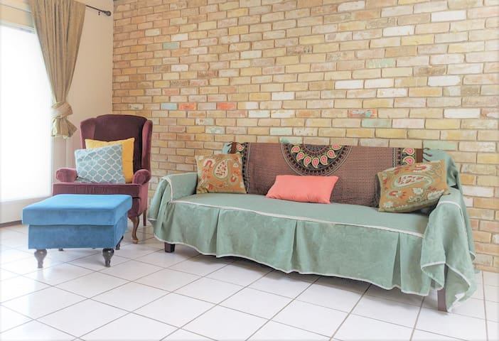 The family room seating area has a comfy antique velvet armchair with ottoman and a Scandinavian style sofa. The green linen and lace sofa cover was handmade by Herman's wife Abi. The sofa can fold flat and be used as a bed.