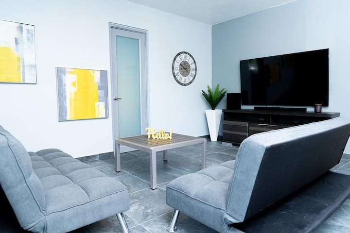 Comfortable living room with large smart tv and sound bar for relaxing after a long day at the Pool or Beach. The futons can sleep additional guests.