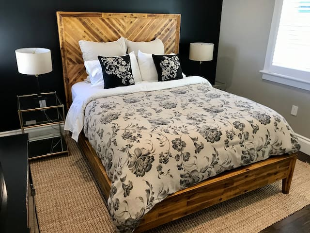 The elegant bedroom features a comfy queen bed with wooden headboard, nightstands and a dresser. Screened windows on either side of the bed let you enjoy the cool bay breeze.