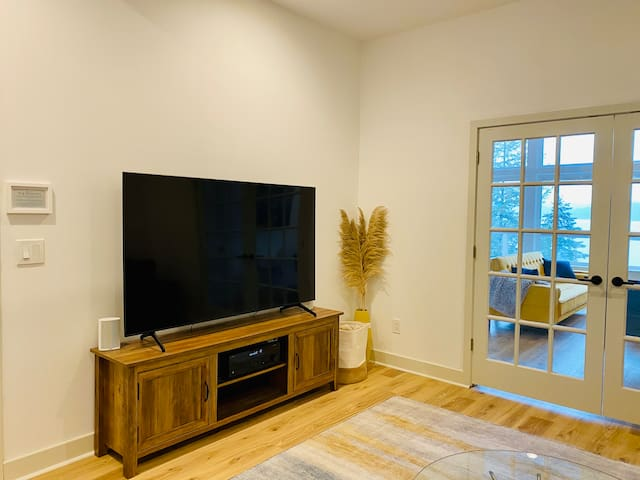 """Downstairs media room with 75"""" smart TV. Media console includes several games and speaker system wired to the entire home."""