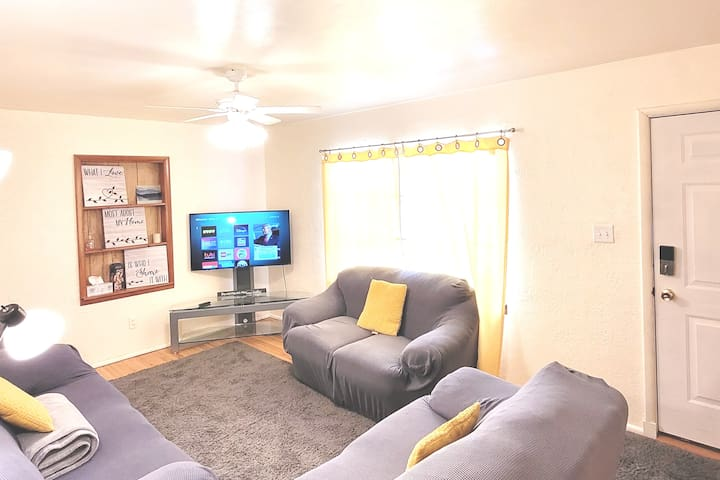 Beautiful living room with 50-inch 4K HD Roku Smart TV, comfortable seating for 8, front door, and decor.
