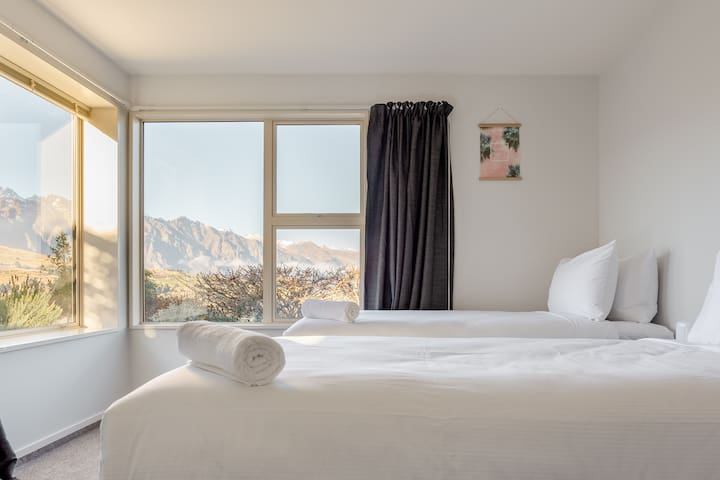 Guest bedroom with 3 long single beds, luxury linens and walk-in wardrobe.  Great mountain, lake and garden views.  We can put 2 Long Single beds into a Super King bed. Notice in advance required.