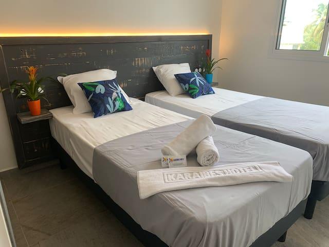 Chambre climatisée avec deux lits de 90 x 200