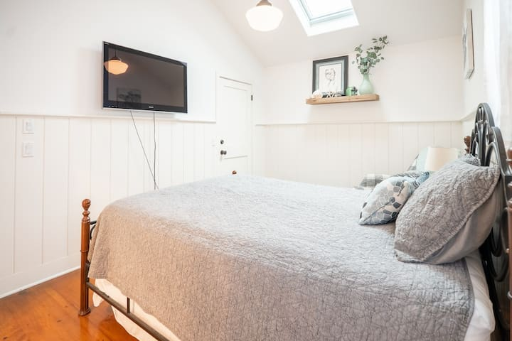 Master bedroom with skylight and TV