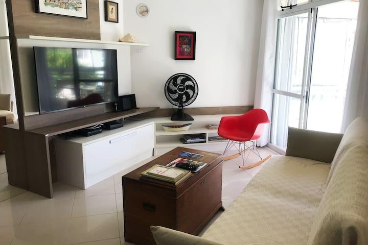Sala de estar equipada com Smart TV 50 polegadas, ventilador e sacada. Disponibilizamos livros para entreter os hóspedes.