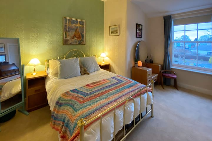 Cosy vintage-style second bedroom with double bed, memory foam mattress, generous drawer storage in vintage furniture, blackout blind with curtains, and plenty of room for a travel cot.