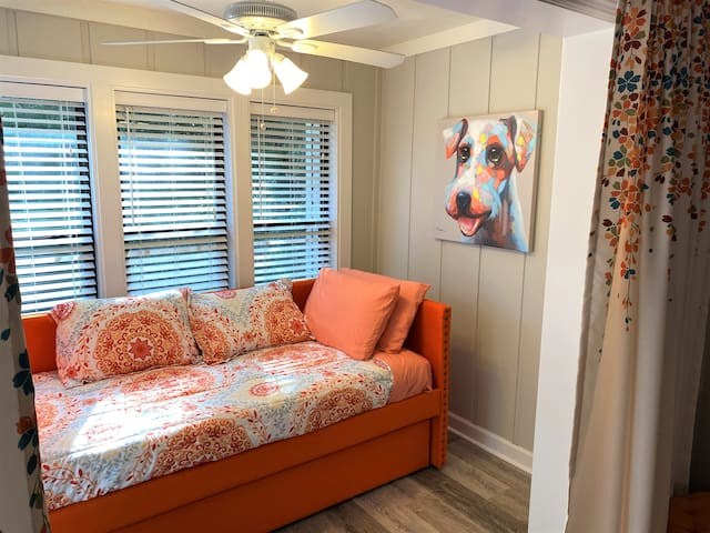 The sunroom is set up as a third bedroom with a trundle daybed to sleeps two, a closet & black-out drapes.