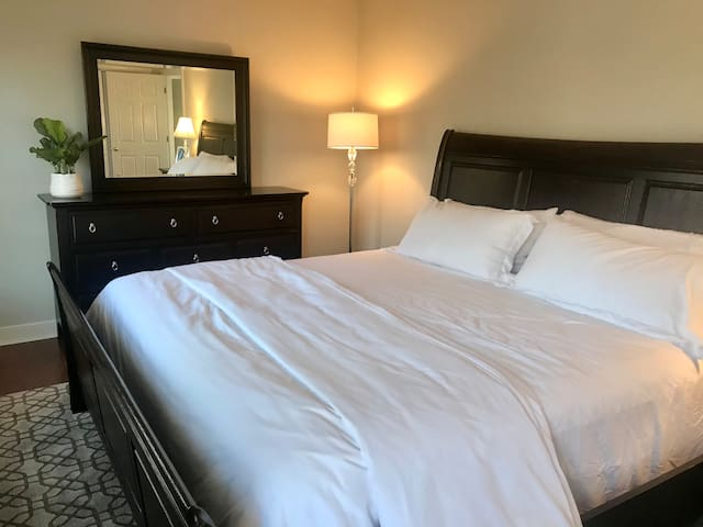 Main level bedroom - very spacious with king bed, dresser, end table, two lamps and ceiling fan. Two windows face the tree- lined street.