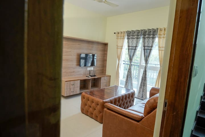 Enjoy the bright and Sunlit Living room with an attached balcony with fresh air and a view of the lush green park or curl up into a cozy and comfortable sofa to binge-watch amazon prime or Hotstar for free on a smart Tv connected to High-speed wifi