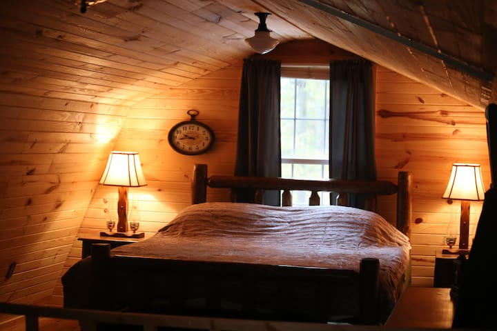 A king-size bed with a brand new Tuft and Needle mattress. The windows look out into the forest.