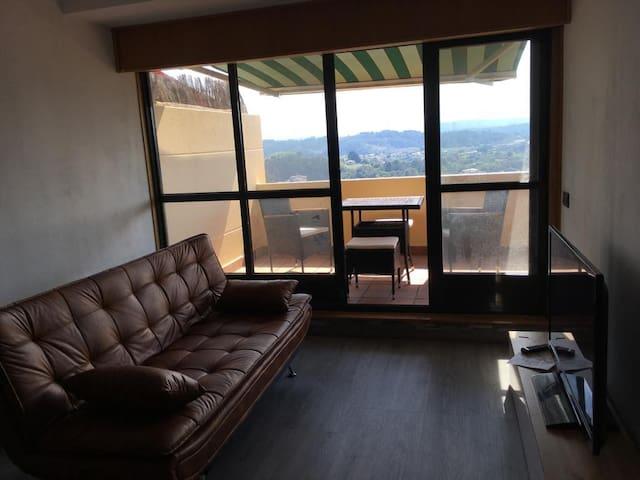 Salón con sofá cama y salida a la terraza y persianas automáticas.