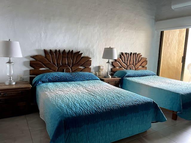 Recámara con dos camas matrimoniales, baño completo dentro de la habitación y AC (Planta Alta)