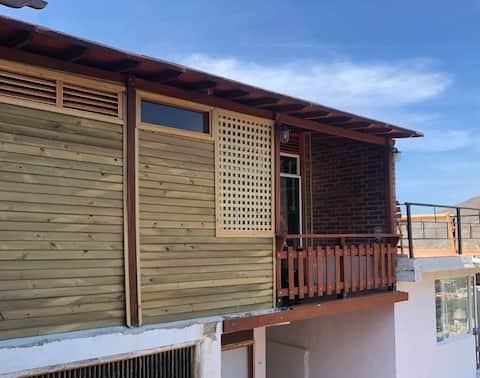 Bungalou frumos din lemn, balcon și vedere la ocean.