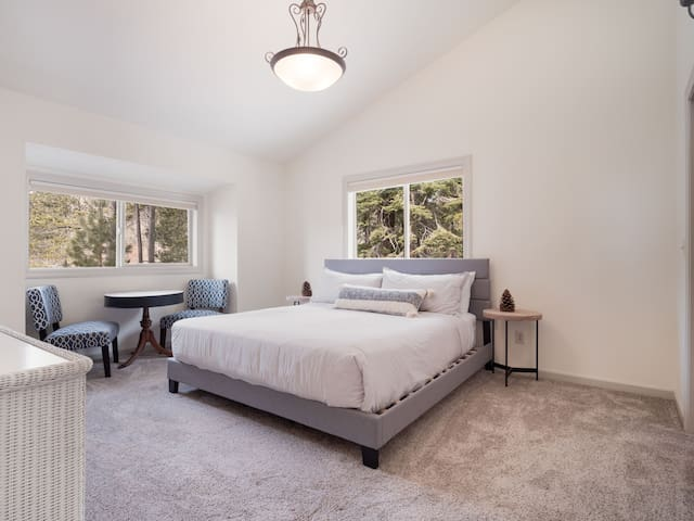 Master bedroom with forest views and a separate seating area to relax, play a board game, or enjoy a drink.