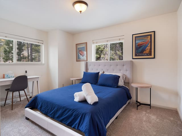 """Large queen bedroom downstairs. Low profile bed and a desk area make this a comfortable sleep/workspace. Tahoe is famous for its wooden boats """"woodies"""" and we give a taste of that in the decor."""