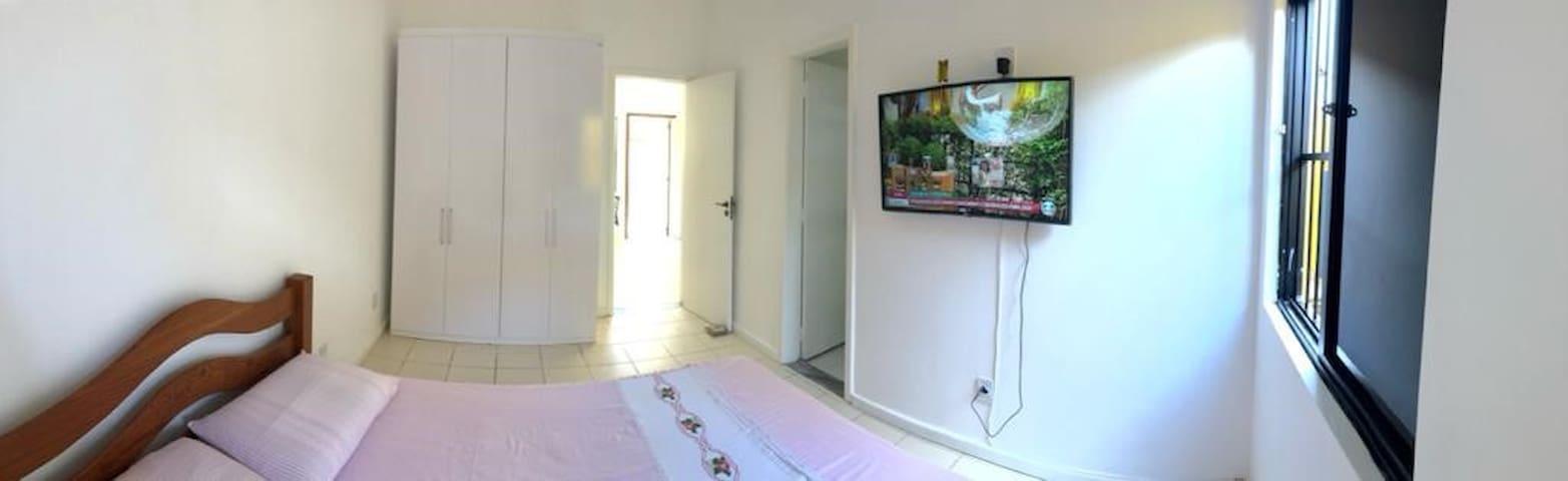 TV, com canais fechados, guarda-roupa, um banheiro. Há dois colchões no chão (forrados e prontos para o uso).