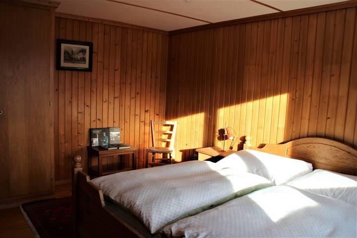 Das geräumige Gästeschlafzimmer im Erdgeschoss mit großem Doppelbett (Zugang vom Wohnzimmer aus)   ..zu lesen gäbe es auch etwas, wer mag :)