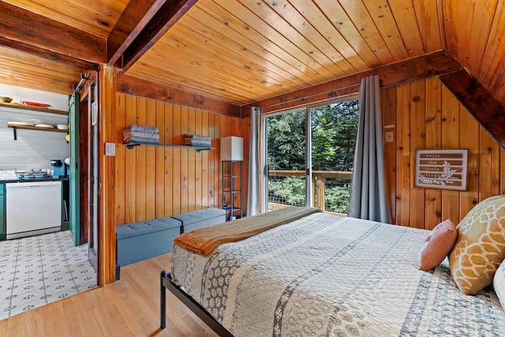 Main floor bedroom with large balcony access. - Queen Bed