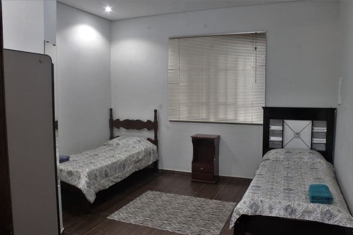 Quarto solteiros com roupa de cama, banho, armário, climatizador e manta.
