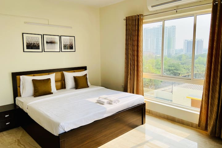 View of Bedroom in daytime, showcasing the large bay windows with lots of natural light. Extra long bed with premium mattress, Flat screen Smart TV with Work Desk & lounge Chair plus Wardrobe. Private Bathroom is attached.