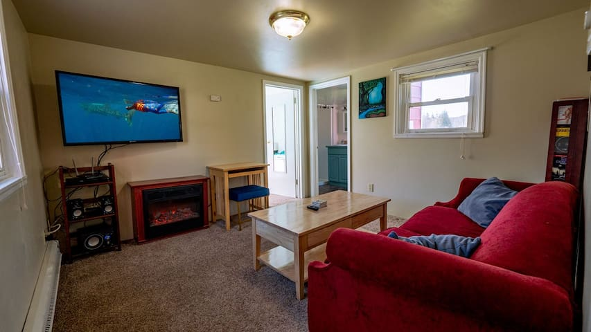 Living room has a large TV with lots of channels, a fun fake fireplace that is a working heater and a small desk.