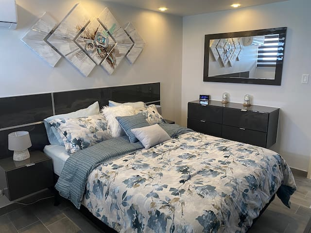 Bedroom with air conditioner,TV, closet, mirror, dresser, to place your belonging in. Beach towel and additional linen in the closet.  The beach chairs are under the bed.