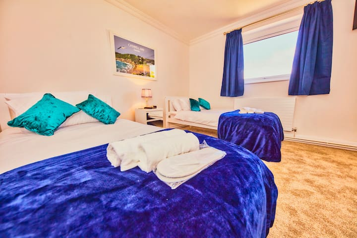 The Caswell Bay Room is our third bedroom and has a view of the rear terrace. We have added a clothes stand and a wall-mounted television. There is also a wash basin, so there is no need to queue for the bathroom.