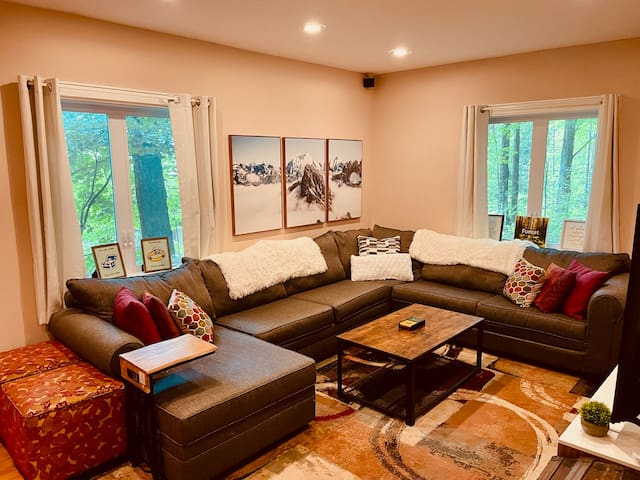 """Downstairs family room w/pullout queen bed, board games,  65"""" Roku TV,  & premium sound for cozy movie/game nights in."""