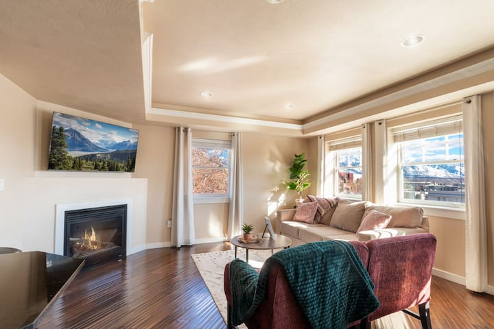 """Open concept living room with beautiful mountain views to the East and downtown views to the West, 55"""" Roku enabled smart TV and fireplace."""