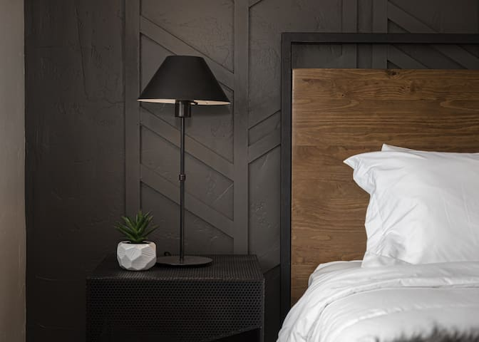 Contemporary furnishings in the upstairs king bedroom suite compliment the warm accent wall behind the headboard.