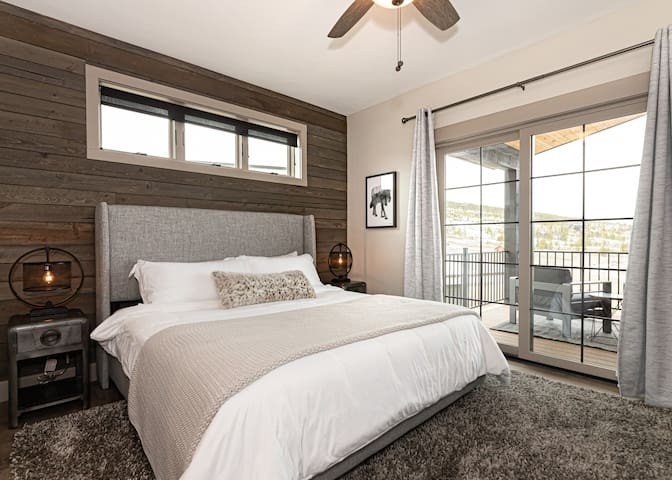 The main floor master suite features a king bed, walk-in closet, attached 5-piece bath, and sliding door access to the covered patio.