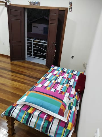 Cama de solteiro no quarto suíte, com visão para a varanda externa.