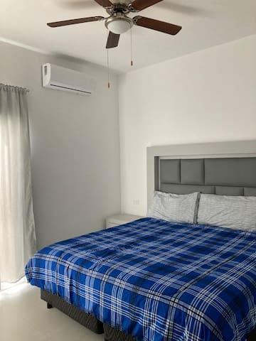 Segunda recámara con cama king size, muebles para colgar y guardar ropa, pantalla plana, ventilador de techo y aire acondicionado.