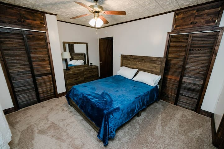 Master bedroom with a queen size bed and ample closet space