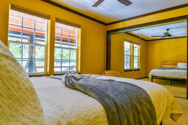 Bedroom two downstairs with large windows overlooking the side yard. Furnished with a queen bed.