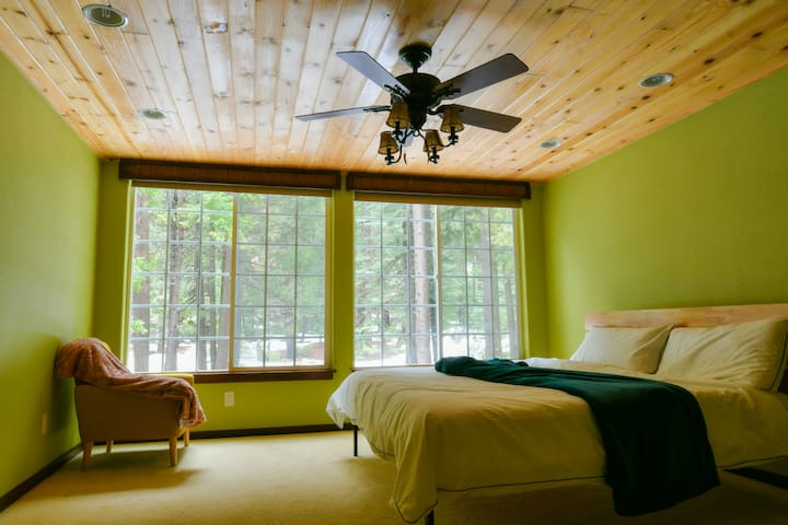 Master Bedroom with King bed. Peer out through large windows into the forest