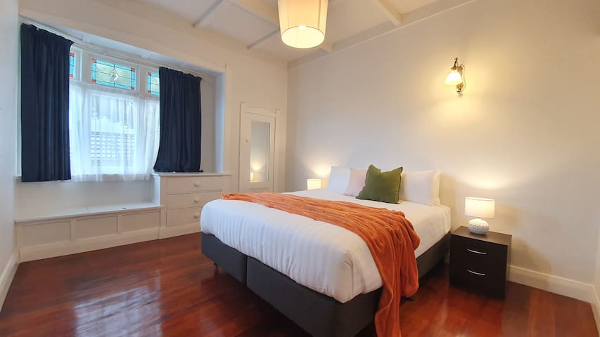 The second ground floor bedroom with builtin   storage and period features like the window seat.