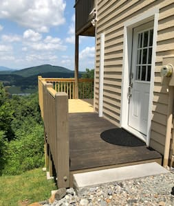 If you park at the bottom of driveway by entrance, the surface is level with the entrance. Driveway is gravel leading to wooden deck entrance.