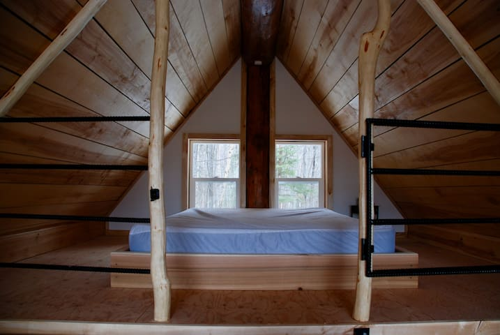 Queen bed in the loft with a mattress cover provided.