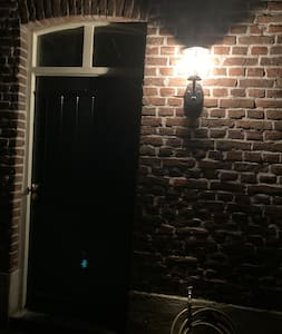 Bij de voordeur hangt een buitenlamp die de oprit verlicht.