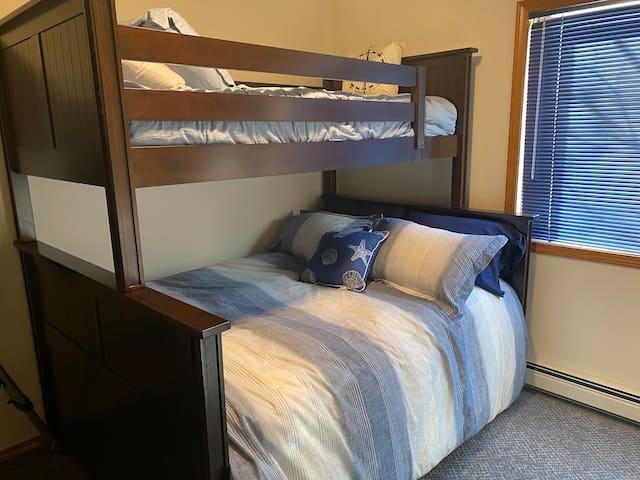Main floor bedroom with queen bed and twin bunk