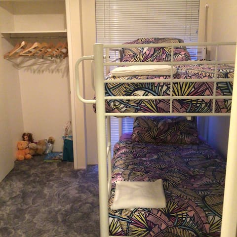 Bunk beds and walk in robe with coat hangers and kids toys