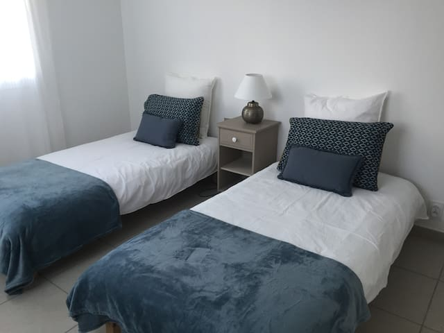 Chambre équipée de deux lits jumeaux, d'un placard avec étagères et  penderie et d'une table de chevet.