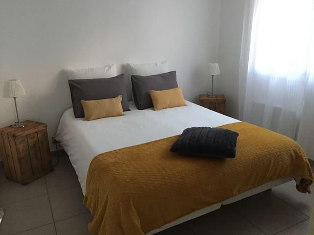 Chambre équipée d'un lit en 160x200, d'une armoire avec étagères et penderie et deux chevets.